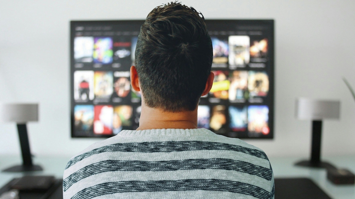 Man watching TV with his back to the camera
